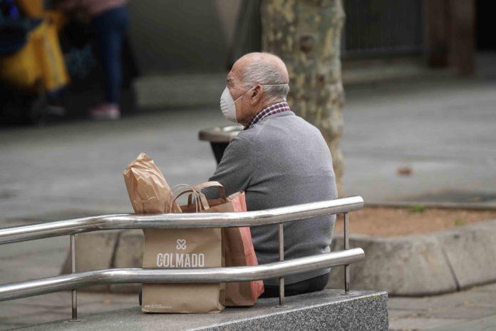 persona mayor sentado en ion banco