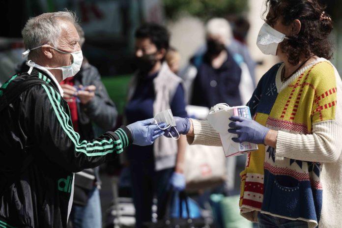 persona de servicios sociales dandole material sanitario a persona sin hogar