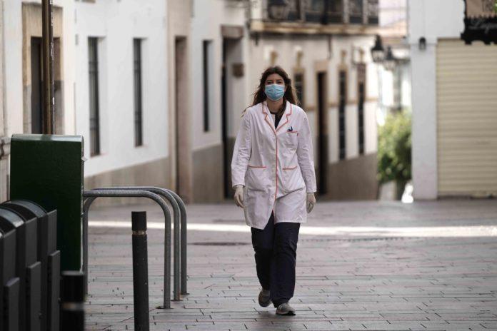 Mujer con bata y mascarilla por la calle