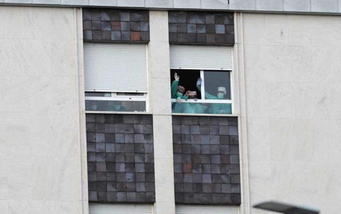 enfermeros asomados a una ventana
