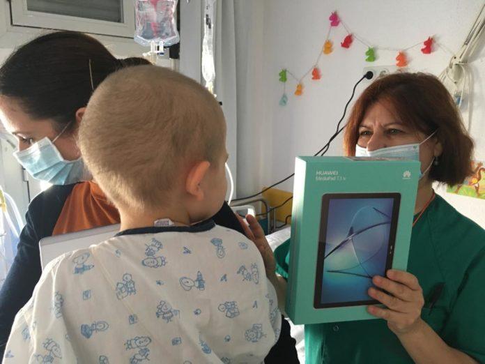Profesional entrega una tablet a un niño durante su estancia