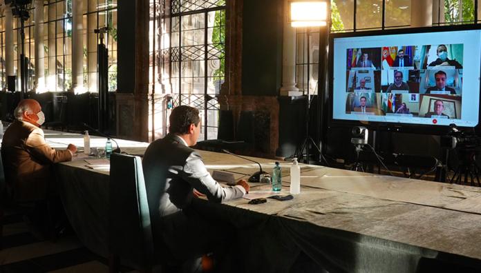 El presidente Juanma Moreno, durante la conferencia mantenida con los alcaldes de las ocho capitales andaluzas.