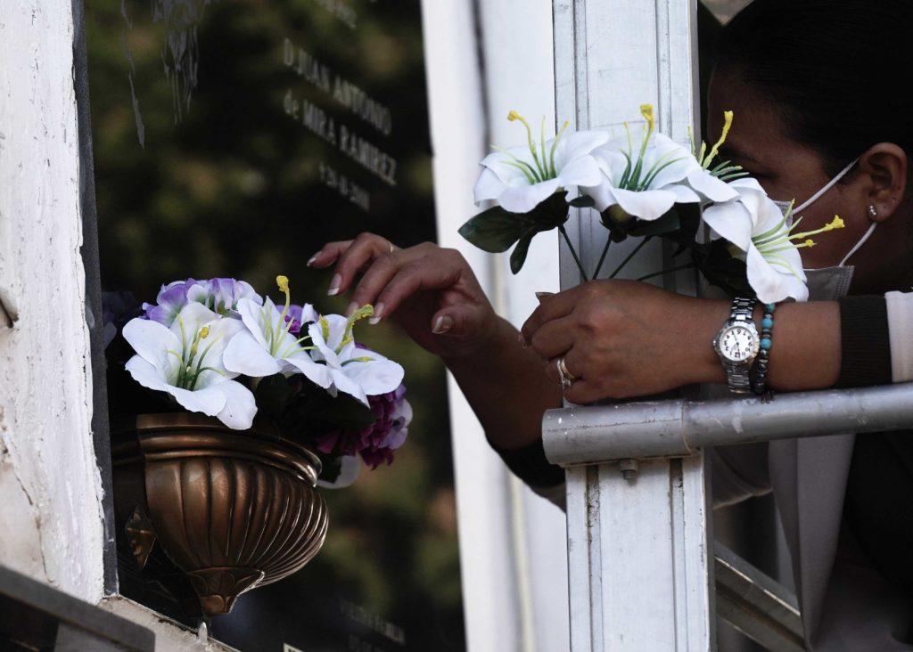 Mujer colgando flores en el cementerio de San Rafael. Foto: RAM