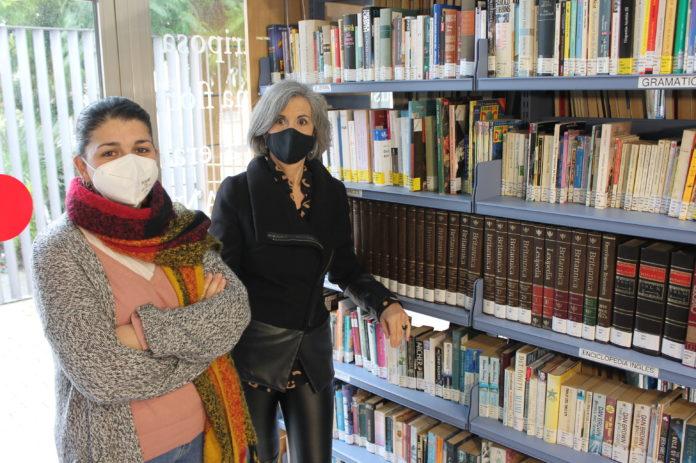 Mamen Beato y Teresa Ferrer posan ante una de las enciclopedias donadas a la Biblioteca