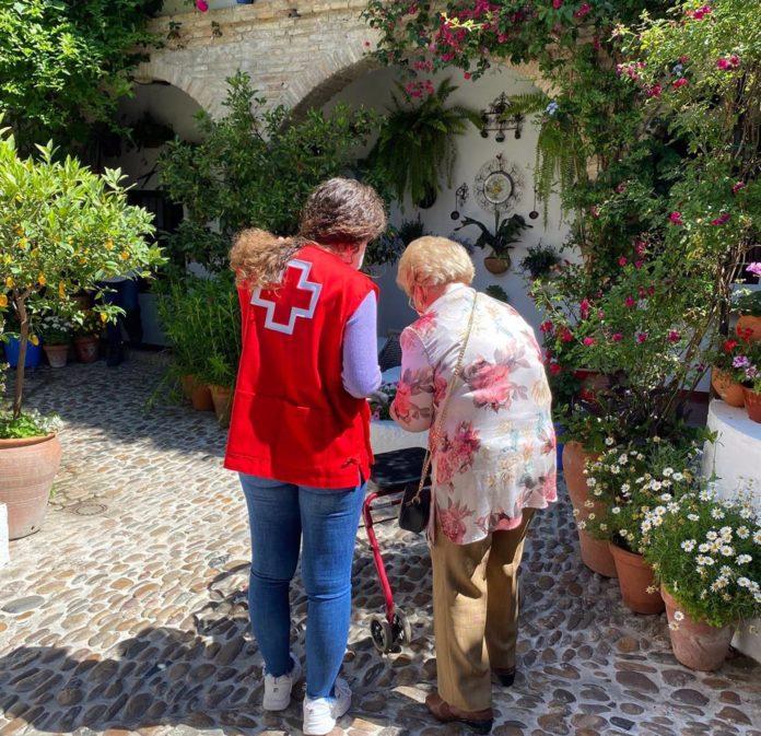 Una persona mayor visita un patio en compañía de una voluntaria de Cruz Roja