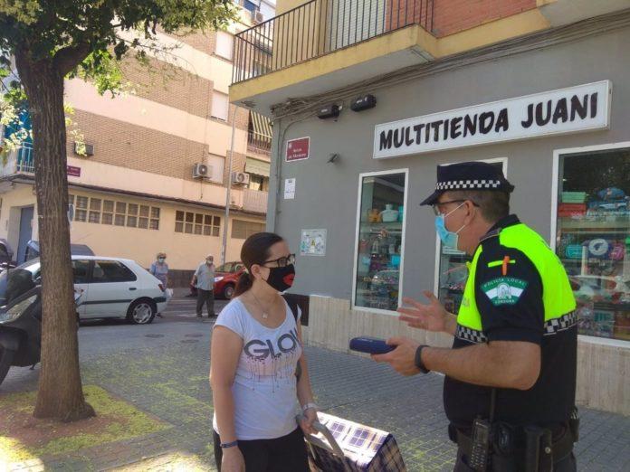 Un policía local de Córdoba habla con una ciudadana sobre el uso obligatorio de la mascarilla